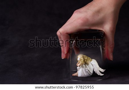 An angel trapped under a glass, a child angel or fallen angel - stock photo
