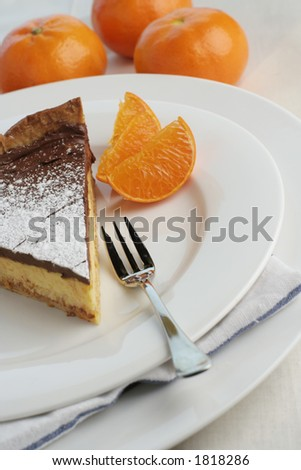 An angle view of a slice of chocolate mocha and orange cheesecake. Table setting with dessert fork and mandarin oranges for styling. Focus point on fork and top of cheesecake.