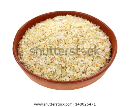 An angle view of minced onion spice in a small clay dish. - stock photo