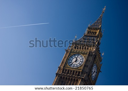 An angled shot of Big Ben, with a aeroplane trail approaching - stock photo