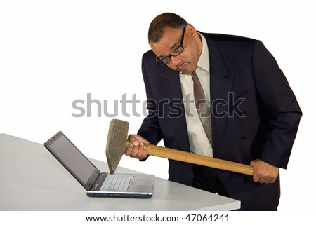 an angry and fierce looking mature African-American businessman  hitting his laptop with a sledgehammer, isolated on white background - stock photo