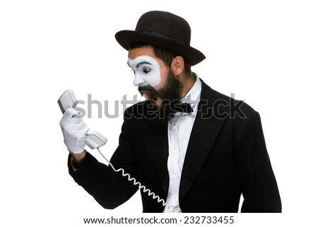 An angry and irritated young man screams into the telephone receiver isolated on white background. The concept of business relations - stock photo