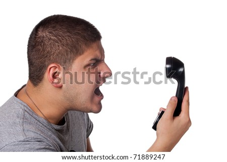 An angry and irritated young man yells into the telephone receiver over a white background.