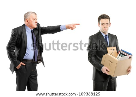 An angry boss firing a man carrying a box of personal items isolated on white background - stock photo