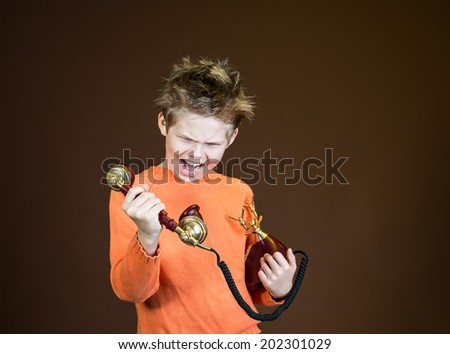 An angry boy screaming in telephone receiver on brown background. Child yelling on a retro phone. - stock photo