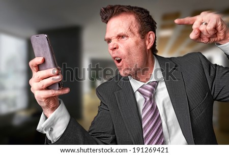 An angry businessman shouting down the phone. Instagram Style Filter Applied. - stock photo