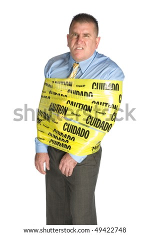 An angry businessman wrapped in caution tape as a warning to coworkers snarls as a result of stress and frustration - stock photo