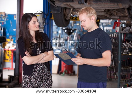 An angry customer talking to a mechanic in an auto repair shop - stock photo
