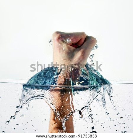 An angry fist punching water isolated on white background - stock photo