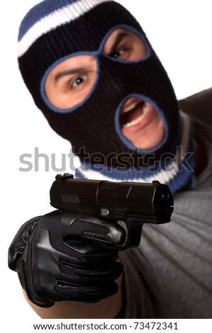An angry looking man wearing a ski mask pointing a black handgun at the viewer. Shallow depth of field with sharpest focus on the gun. - stock photo