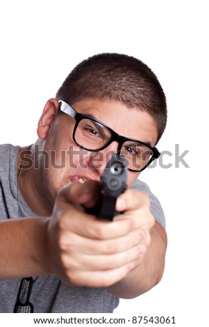 An angry looking teenager wearing black frame glasses points a black handgun at the viewer. Shallow depth of field with focus on the face.