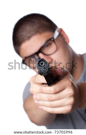 An angry looking teenager wearing glasses pointing a black handgun at the viewer. Shallow depth of field.