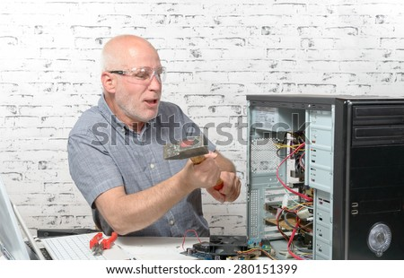 an angry man destroy his computer with a hammer - stock photo