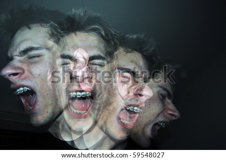 An angry man screams out of control in the darkness. He is a white Caucasian young adult wearing braces on his teeth. - stock photo