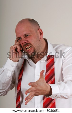 An angry man talking on a mobile phone in shirt and loose tie - stock photo