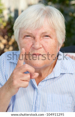 An angry senior woman, wagging her finger and scolding.