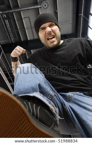 An angry thug beating me while I'm down on the ground. - stock photo