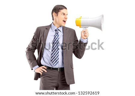 An angry young businessman announcing via megaphone isolated against white background - stock photo