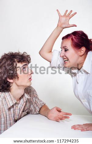 An angry young woman brandishing her husband on a light background - stock photo