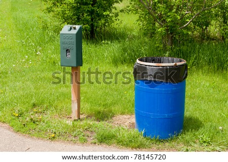 An Animal Waste Bag Dispenser by a Blue Trash Can in a Park - stock photo