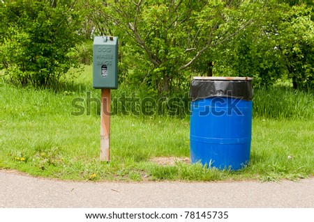 An Animal Waste Bag Dispenser by a Blue Trash Can in a Park