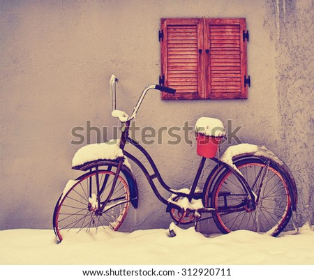 an antique bike with an empty pot on the seat in winter covered in snow toned with a retro vintage instagram filter app or action effect  - stock photo