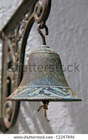An Antique Brass Bell Hanging From A Wall - stock photo