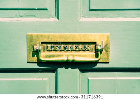 An antique brass letterbox in a wooden front door - stock photo