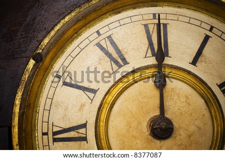 An Antique Clock Face with gold gilding and roman numerals.