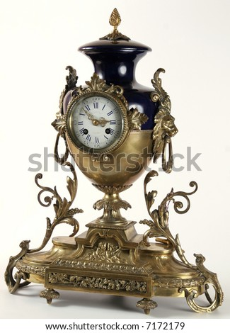 An antique clock with bronze animal and floral forms.