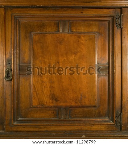 An antique cupboard door with brass keylock and hinges