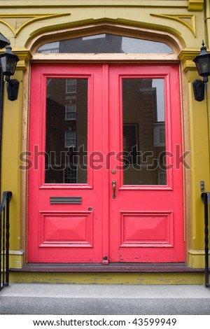 An antique doorway with red painted doors. - stock photo