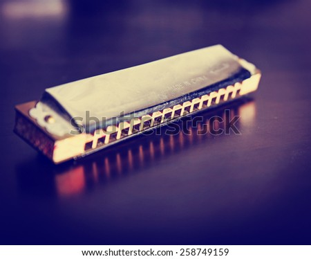 an antique harmonica on a wooden table toned with a vintage retro instagram filter effect app or action - stock photo