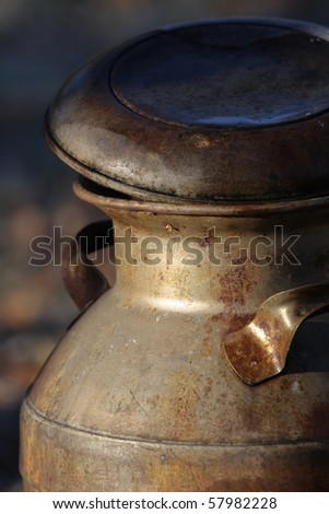 An antique milk container, aged and rusted by the passage of time - stock photo