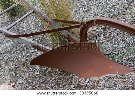 An antique plough sits quiet in the dirt. - stock photo