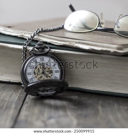 An antique pocket watch, glasses and bible in close up - stock photo