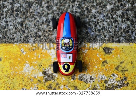 An antique race car, made before 1950s, parks on the yellow painting. - stock photo