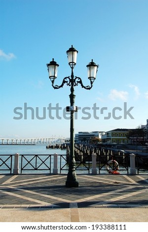 An antique street lamp with sky as background beside seaside