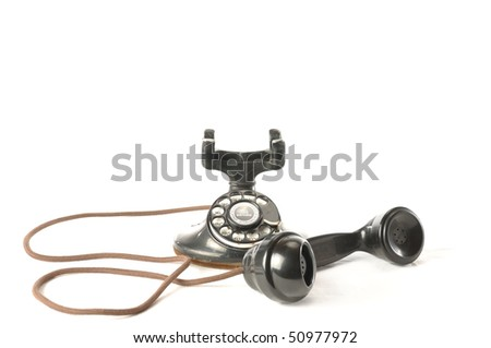 An antique telephone with handset off the hook