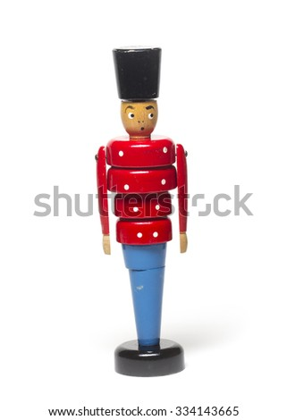 An antique toy soldier with blue pants, red jacket, black hat, and a surprised expression isolated on a white background.    - stock photo