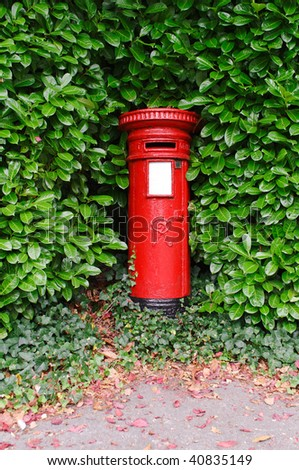 An antique Victorian UK post pillar surrounded by green leaves. - stock photo