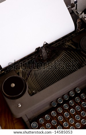 An antique, vintage typewriter with a blank piece of paper for message or copy, image includes keyboard and carriage - stock photo