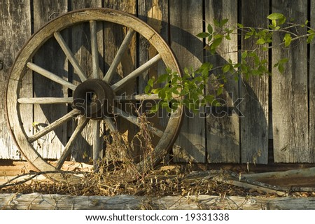 An antique wagon wheel photographed in the warm late afternoon sun which casts shadows against the barn. - stock photo