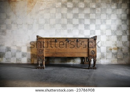 an antique wooden chest of drawers in castle at a stone wall - stock photo