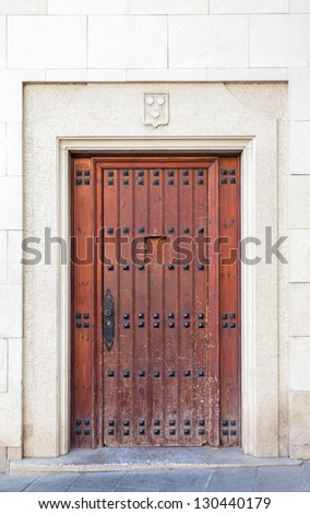An antique wooden door with studs that has a certain medieval flavor to it. Shot in the Sarri�  quarter of Barcelona, where old wooden doors are still typical, specially in historical buildings. - stock photo