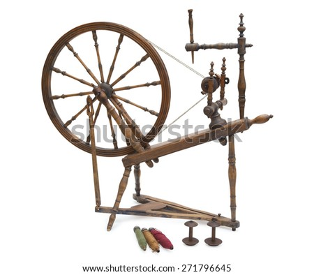An antique wooden spinning wheel with yarn and bobbins isolated on a white background