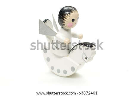 An antique wooden xmas decoration of an an angel riding a rocking horse, isolated against a white background. - stock photo