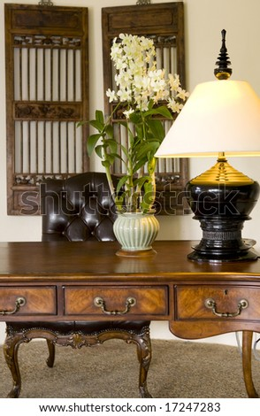 An antique writing desk and leather chair with decorated with a lamp and flowers - stock photo