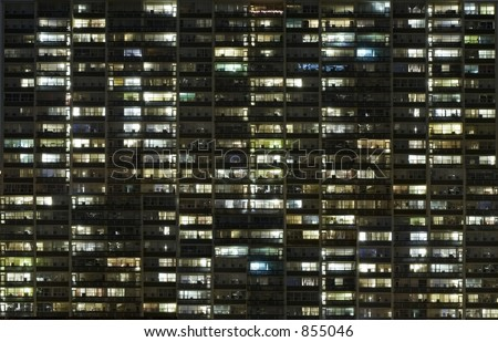 An apartment at night with lights. Arranged in a grid. - stock photo
