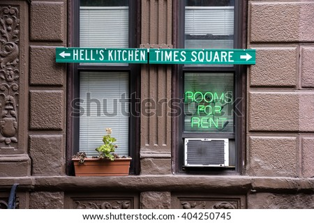 An apartment building with a neon sign in the window for room rentals in Manhattan. - stock photo